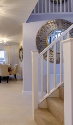 Entry hall with high end luxury stairway carpet with white natural wooden spindles both sides sweeping to the first floor where the wooden spindles continue till the master bedroom! Dining room with garden view at the bottom of this magnificent coastal house in Scotland!