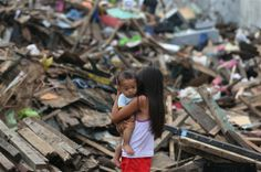 A girl survivor holds her brother as they walk along debris from damaged homes at typhoon ravaged Tacloban city, central Philippines on Satu...