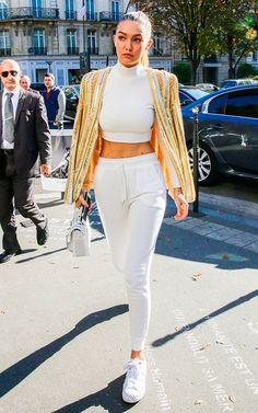 Gigi Hadid com look estiloso de cropped top com tira no pescoço, calça de moletom e tênis branco com jaqueta dourada