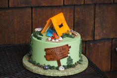 Green camping themed birthday cake with orange tent topper