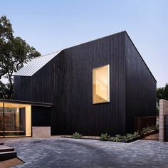 This black-stained wooden extension extends a family home in Texas. See more photos at dezeen.com/tag/texas #architecture #extensions by dezeen