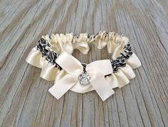 """Ivory & Black Paw Print Garter Embellished With Ivory Satin Bow and Rhinestone Paw Print Accent For The Perfect Touch.    *******PLEASE LEAVE YOUR WEDDING DATE AT CHECKOUT*****    ** Garter measures: 1.5"""" W **    * Garter listing is for standard size, if interested in custom size please contact prior to purchasing. *   Shop this product here: http://spreesy.com/BellaDivaCouture/396   Shop all of our products at http://spreesy.com/BellaDivaCouture      Pinterest selling powered by Spreesy.com"""