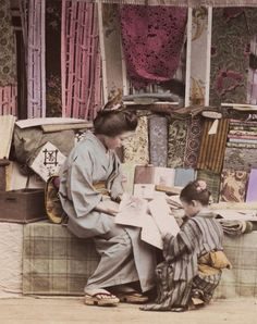 Woman inspecting kimono samples at a cloth merchant store.  Hand-colored photo, circa 1890, Japan.  Photographer unknown