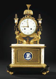 Pendule en bronze doré, marbre peint, émaux, biscuit de porcelaine et verre églomisé de la fin de l'époque Louis XVI, le cadran signé Revel / A PARIS