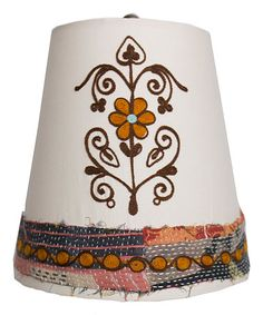With intricate embroidered details and a bold design, this vintage-inspired shade adds a touch of earthy charm to lamp bases.