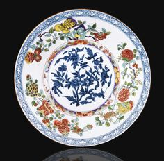 A MEISSEN PORCELAIN PLATE, CIRCA 1735 decorated in underglaze blue flowering branches in the center and in the style polychrome porcelain green family drilled rocks flowery lace to cross on the edge; marked with crossed swords in blue