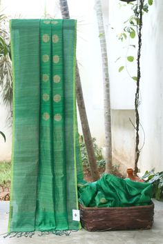 THE GORGEOUS DARK GREEN BAILOU MATKA SILK HAS GOLD POLKA DOTSACROSS THE BODY. THE SUBTLE GOLD AND GREEN BORDER FLOWING INTO THE PALLU MAKES THE SAREE BEAUTIFUL.