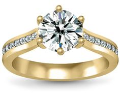 Six Prong Channel Diamond Ring in Yellow Gold  Eighteen round cut diamonds are channel set in this elegant six prong trellis diamond ring setting in yellow gold, accenting your choice of center diamond. 1/5 carat total diamond weight and proudly made in the USA.      Retail Price: $1,815.00 Price: $725.00