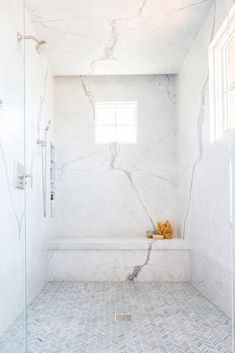 Walk into a large master bathroom shower to admire thin gray marble herringbone floor tiles and marble slab walls featuring stacked shower niches and a marble shower bench. Source by Master Bathroom Shower, Shower Niche, Bathroom Showers, Bathroom Ideas, Shower Ideas, Cultured Marble Shower Walls, Carrara Marble Bathroom, Bathroom Renovations, White Marble Bathrooms