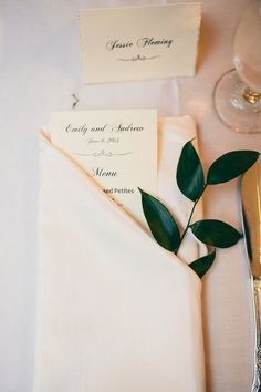 Elegant place settings included a menu and a sprig of ruskus tucked in the folded napkin.