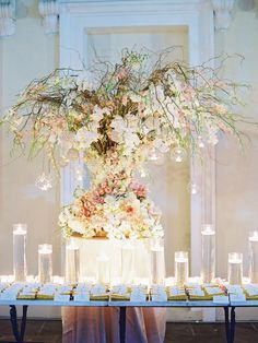 absolutely stunning floral bouquet with orchids, roses ad other white pink, orange and green flowers on the escort card table with hanging tealights http://www.itgirlweddings.com/blog/new-years-eve-black-tie-wedding