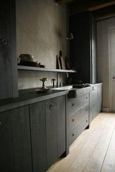 Cette déco cuisine avec évier en pierre noir et murs béton ciré grège prend le parti d'utiliser le gris anthracite en peinture pour les meubles de cuisine en bois.