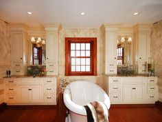 A white slipper tub takes center stage in this luxurious bathroom. Framed by two separate vanity cabinets, this room has plenty of storage space. A brass sconce light illuminates each vanity while a diamond-patterned tile covers the walls for added visual interest.