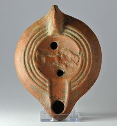 Roman oil lamp with charioteer, 3rd-4th century A.D. North Africa colonies, redware terracotta lamp, mouldmade, with discus adorned with a charioteer in a biga of horses, concentric circles outside the discus, large M within raised circular base, 12.7 cm long. Private collection