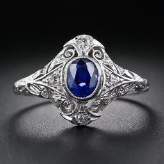 This stunning and splendid original Edwardian sapphire and diamond ring - circa 1910-1920 - features a faceted oval royal blue sapphire, weighing one carat, bezel-set atop an elegantly handcrafted platinum and diamond mounting. The magnificent setting is replete with delicate and lacy, decorative open work. A fully hand engraved ring shank adds the finishing flourish to this enchanting and consummate antique jewel.