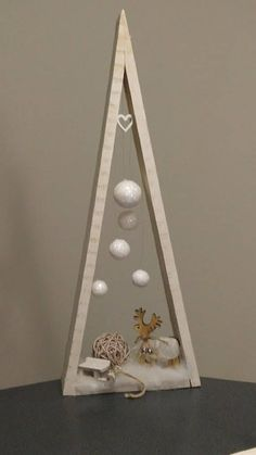 Christmas decoration in bleached wood, to ask. Triangular shape reminiscent of a fir tree, inside a reindeer on the snow, with a wooden sledge and hanging white balls, surmounted by a small heart in white wood. Outside Christmas Decorations, Christmas Wood Crafts, Wood Christmas Tree, Modern Christmas, Christmas Projects, Simple Christmas, Christmas Diy, Christmas Ornaments, Christmas Houses