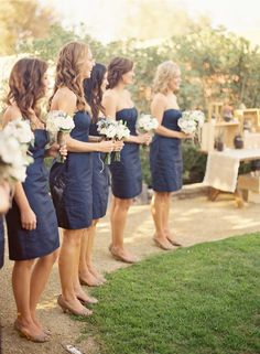 Navy bridesmaids, nude heels, and white bouquets.