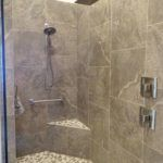 Large Rain Shower with accent floor and foot rest for shaving.