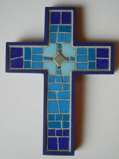 This mosaic cross is made with vitreous glass tiles in four shades of blue from dark majolica to sky blue. The center has a silver tile with glass