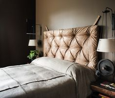 Padded leather headboard, dark feature wall and unique bedside lamps complete this masculine bedroom