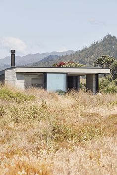 The Coromandel's gritty persona marries smooth-cut family living in this neutral-hued home, designed by Neu Architecture. Slide Screen, New Zealand Houses, Exposed Concrete, Dining Room Walls, Main Entrance, The Dunes, Clever Design, White Walls, Outdoor Structures