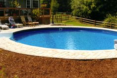 Freedom above ground pool installed completely inground with paver deck, stairs, and hopper bottom.