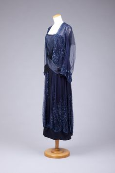 1923. Navy silk satin dress with navy sequined net overlays. Has cream lingerie silk dress shield in bodice. Two front navy satin sashes cross at waist and drape to back and form bow at hip level. Sequins on cuff of net sleeve. Goldstein College of Design.