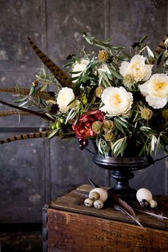 An elegant Thanksgiving centerpiece is arranged with peonies, greenery & pheasant feathers.