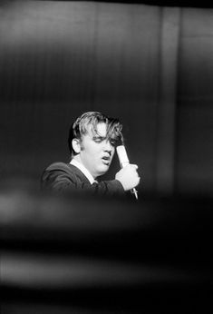 Elvis Presley sings a ballad before his teenageaudience in the darkness of the Mosque Theatre,Richmond, VA.June 30, 1956.
