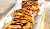 PARMESAN-CRUSTED CHICKEN QUESADILLAS Weizentortillas mit suatiertem Hühnerfleisch, Tomaten-Basilikum Mix, knusprigem Speck und Monterey Jack Käse gefüllt, danach mit Parmesanpanade umhüllt und goldbraun gebraten, garniert mit Balsamic Glaze.