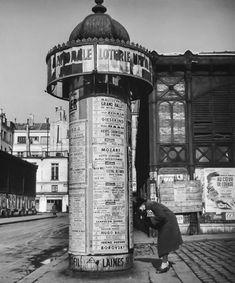 La pub était collée sur les colonnes Morris. / The Morris column. / / By Robert Doisneau, 1946.