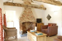 Here is a traditional countryside cottage living room at Romulus & Remus in Norfolk. Brick chimney breast, exposed beams and wicker chairs.
