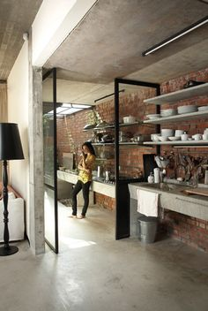 Indoor / Outdoor kitchen separated by steel doors - Modern architectural detail - Concrete floor - Exposed brick wall