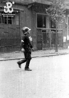 Young insurgent Zbigniew Ślężakowski 'Kędziorek' walks down ul. Zgoda. He is wearing a  fireman's helmet.