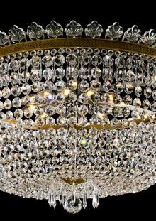 Regency bag chandelier. Antique brass metalwork with strands of double pointed octagonal buttons create this bag style chandelier. The main ring with a decorative brass gallery is dressed with crystal leaves and icicles. Finished with a 60mm faceted crystal finial. Contains 12 internal lights