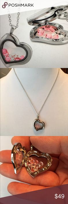 """NWOT CRYSTAL-FILLED HEART LOCKET PENDANT Rhodium-plated heart-shaped pendant is filled with free-moving pink and white crystals. Locket has clear double windows and can be opened and closed to change crystals if wanted. Rhodium plating is over brass construction. Rolo chain is 18"""" and has a lobster claw clasp. Pendant dimensions are 1.5"""" x 1.5"""" x 1.5"""". Jewelry Necklaces"""