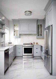 This gray u-shaped kitchen features a gray paneled hood flanked by antiqued mirrored kitchen cabinets and mounted against white and gray mosaic backsplash tiles over a stainless steel oven range. Marble Floor Kitchen, Best Flooring For Kitchen, Best Kitchen Cabinets, Kitchen Cabinet Design, Gray Cabinets, Corner Cabinets, Tiles Design For Kitchen, Kitchen Tile Flooring, Grey Kitchen Designs