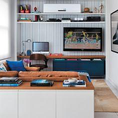 """Cansada de conviver com o escritório dentro do seu quarto, a moradora deste apartamento pediu às arquitetas cariocas Patricia Carvalho e Adriana Valle que projetassem um ambiente reunindo a TV de 55"""" e o computador. """"Fizemos uma bancada de madeira de ponta a ponta, que serve de mesa de trabalho. Embaixo dessa prancha, um módulo laqueado de azul-marinho guarda documentos, pastas e os DVDs da família"""", explica Patricia. Embora fique integrado à sala de estar, o cantinho tem personalidade…"""