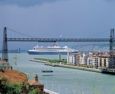 Queen Mary 2 moored at the cruise pier in Getxo. In the foreground the Bizkaia Bridge that links the towns of Portugalete y Las Arenas.