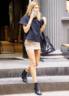 Hailey Baldwin steps out in a dark blue top, tan suede skirt, black booties and a tote bag.