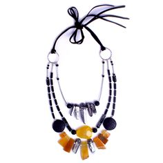 The mix of warm yellow agates and cool silver hematite gives rise to wild & elegant glamour in this one of a kind statement necklace. Three strands of Quartz, Agates, Magnesite, Lava and Hematite show off the hues of yellows, orange, silver, lead and black. Suede strings allow you wear the necklace as a shortie or to leave it long, which means you will find occasion time and again to incorporate into your wardrobe. Like all our pieces it is one of a kind, handcrafted with love and care in…