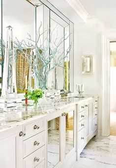 Glam master bathroom with white mirrored double bathroom vanity, marble countertops, double sinks, marble tiles floor, yellow & gray, chevron pattern shower curtain and manzanita branches painted pale blue.