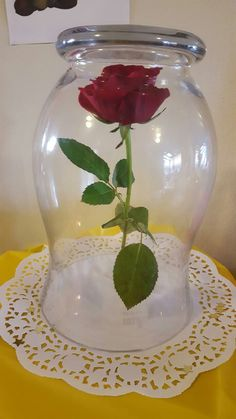 Beauty and the beast party table setting.  The rose. An upside down vase with a fresh rose.