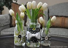 Lovely alternative to a vase! Glass jar decorated with scrapbook design paper, ribbon and buttons. Ad tulips, lovely!