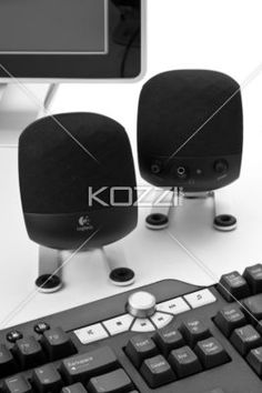 Logitech Computer Speakers - Closeup of a pair of Logitech computer speakers with partial keyboard and monitor in view against a white background.