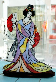 Una joven geisha vestida en un hermoso kimono está bailando con los fans. Parece un personaje de viejo japonés imprimir. Esta chica encantadora puede decorar su sala de estar o dormitorio. Utilizamos el vidrio Spectrum y Wissmash cuando hacen esta lámpara. La cara se pinta con marcos de