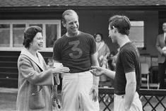 1967 Queen Elizabeth awarding Prince Philip and Prince Charles with trophies after a polo match.