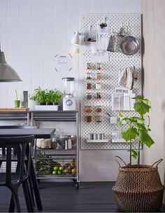 White SKÅDIS pegboards attached to a kitchen wall next to a worktop with accessories to hold recipes and smoothie ingredients