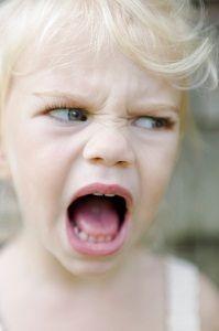 Headshot of angry young child yelling