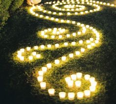 Small tea candles decorate the ground leading to the entrance of the backyard and the areas around the outdoor tents.